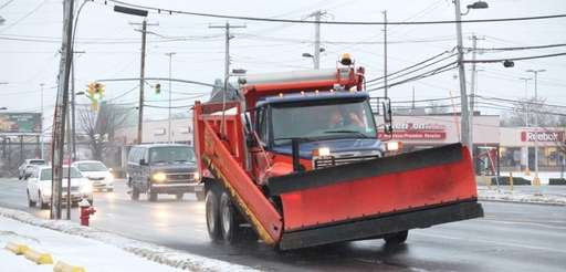 Cars and a plow navigate through the wet