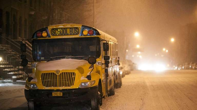 A school bus stays parked in a snow-covered