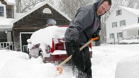 Craig Clasen uses a shovel to clear his