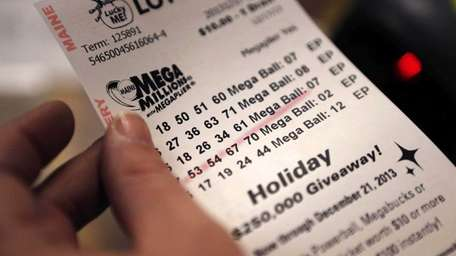 A cashier holds a Mega Millions lottery ticket