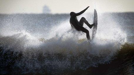 A surfer enjoys the frigid surf after dredging
