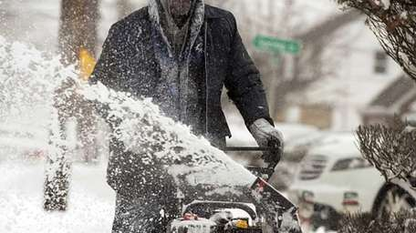 Roosevelt resident Jerome Williams clears snow off the