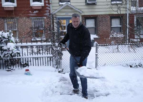 New York City Mayor Bill de Blasio shovels