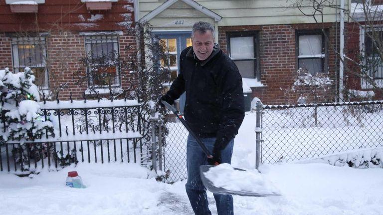 New York City Mayor Bill de Blasio shovels