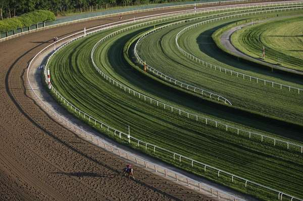 A horse gallops around the fourth turn of