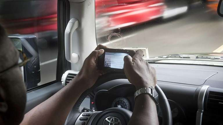 This file image shows someone texting while driving.