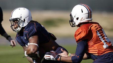 Auburn quarterback Nick Marshall, right, hands off the