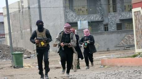 Gunmen patrol during clashes with Iraqi security forces