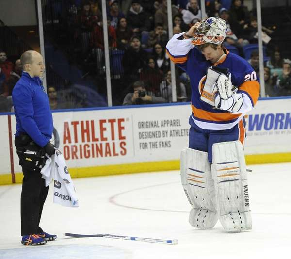 An Islanders trainer watches goalie Evgeni Nabokov (20)