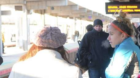 Commuters wait for a train Wednesday morning at