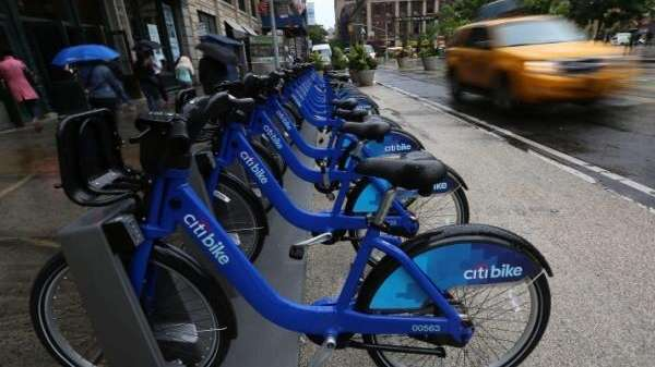 A rack of Citibike bikes awaits riders. The