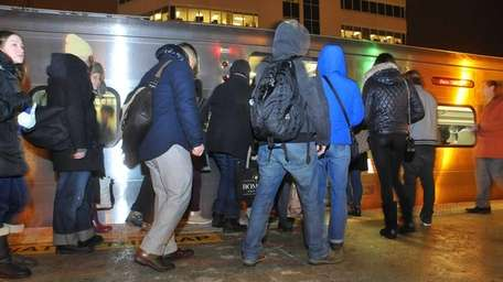 Commuters board their westbound train while other passengers