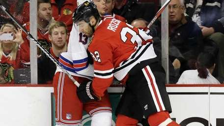 Rangers' Daniel Carcillo, left, is checked by Chicago