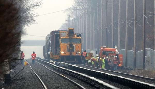 A crane works on the freight train derailment