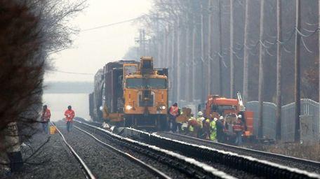 A crane works on the freight train derailment