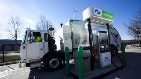 Trucks refuel at a natural gas refueling station
