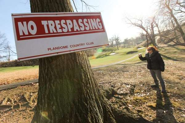 "Sherry Klein stands beside a ""no trespassing"" sign"