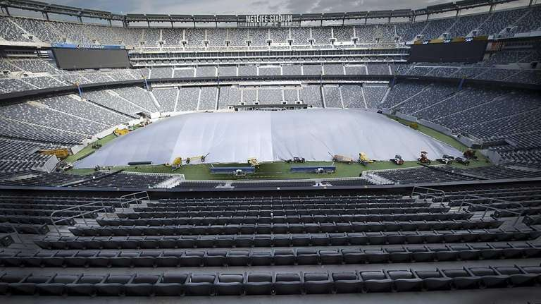 Crew members cover the field with tarp at