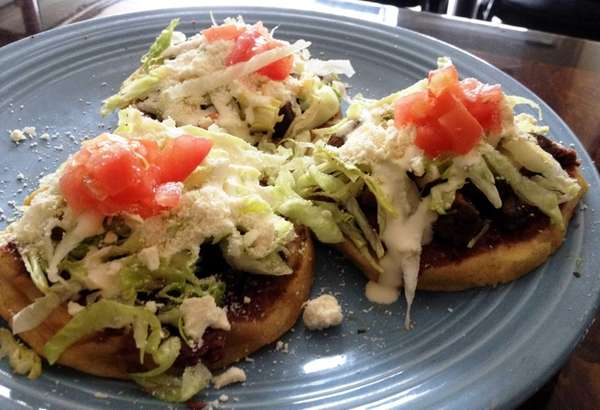 Sopes are topped with beans, tongue, lettuce, tomato,