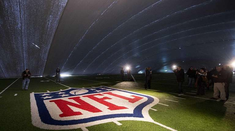 The NFL logo at the fifty yard line