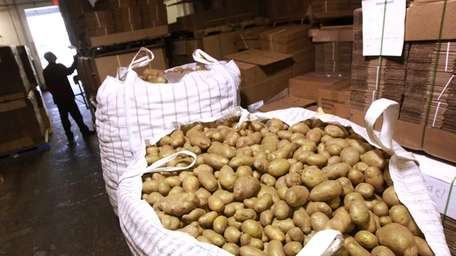 Russett potatoes, which come in 2,000-pound bags, wait