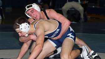 Rocky Point's Thomas Dutton (black singlet) defeated Huntington's