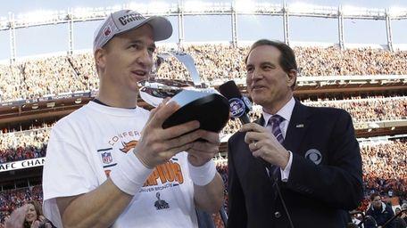Denver Broncos quarterback Peyton Manning, left, accepts the