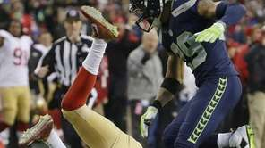 San Francisco 49ers' Colin Kaepernick is tripped up