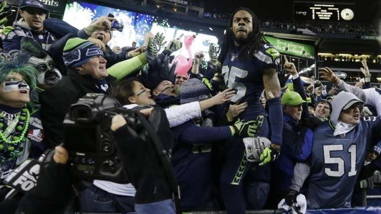 Seattle Seahawks' Richard Sherman celebrates with fans after