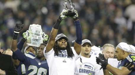 Seattle Seahawks' Richard Sherman holds up the George