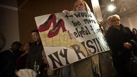 Theresa Moran, of Island Park, holds a sign