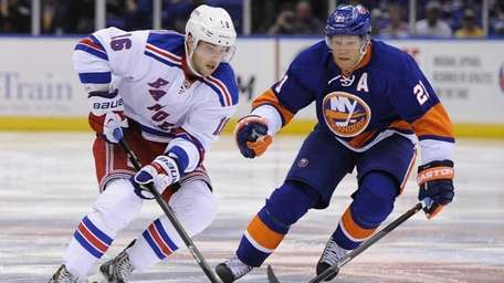 Kyle Okposo defends against Derick Brassard in the