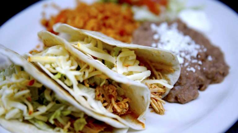 A platter of soft tacos filled with chicken