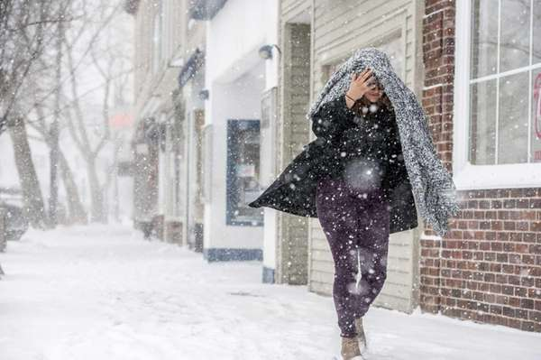 A woman braves the elements on Main Street