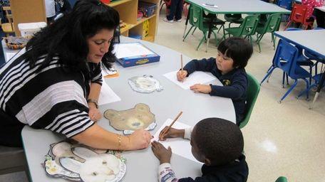 Pre-kindergarten teacher Angela Tirone helps student Jarrell Love,
