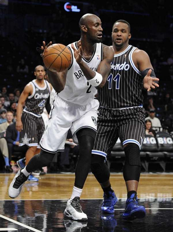 Nets forward Kevin Garnett passes under the basket