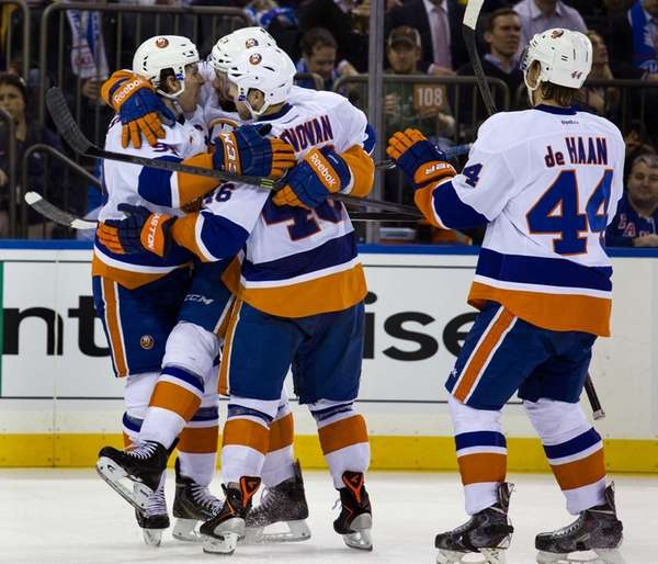 Islanders' Colin McDonald is hugged by teammates Matt