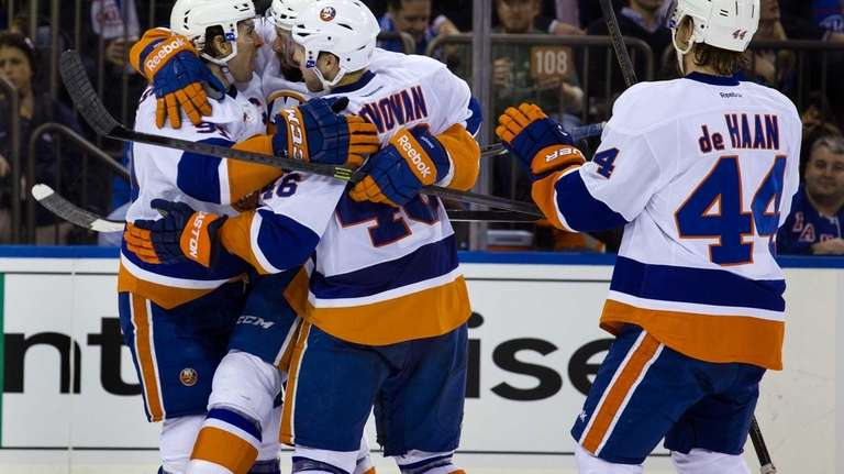 Islanders' Colin McDonald is hugged by teammates Matt