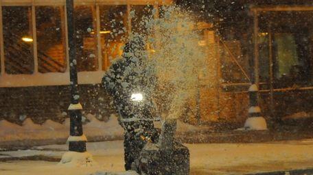 A man clear aways snow using a snowblower