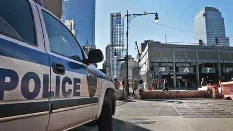 A police vehicle sits near a mechanical barricade