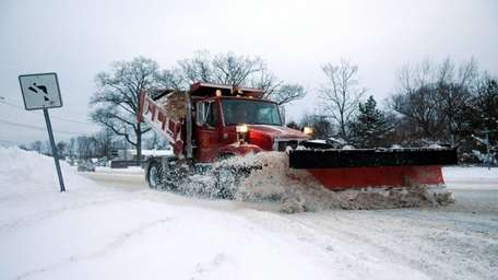 A Brookhaven town plow truck clears away snow