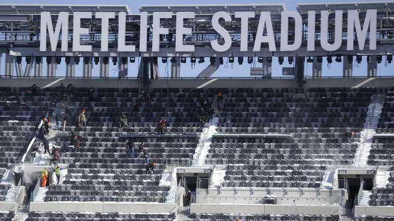 Workers shovel snow off the seats at MetLife