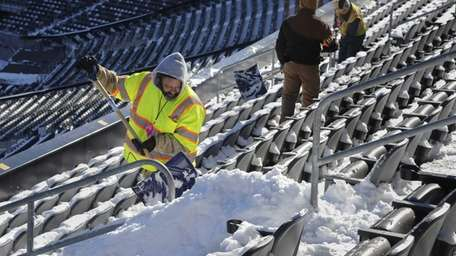 MetLife Stadium workers shovel snow from the stands
