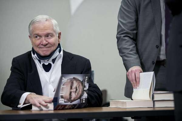 Former U.S. Secretary of Defense Robert Gates signs