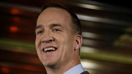 Denver Broncos quarterback Peyton Manning talks with reporters