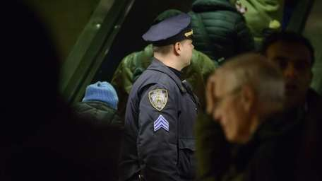 An NYPD officer watches passengers as they arrive