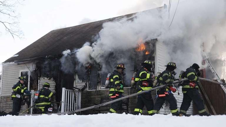 Firefighters battle a fire at a home on