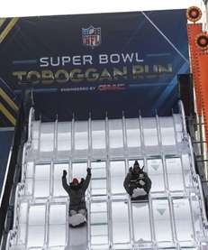 People slide down the Super Bowl Toboggan Run,