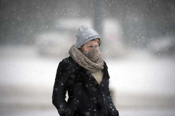 A woman endures the weather while waiting for