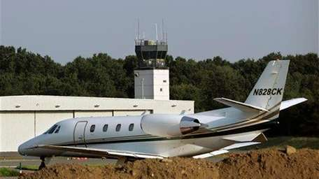 A plane taxis past a control tower at